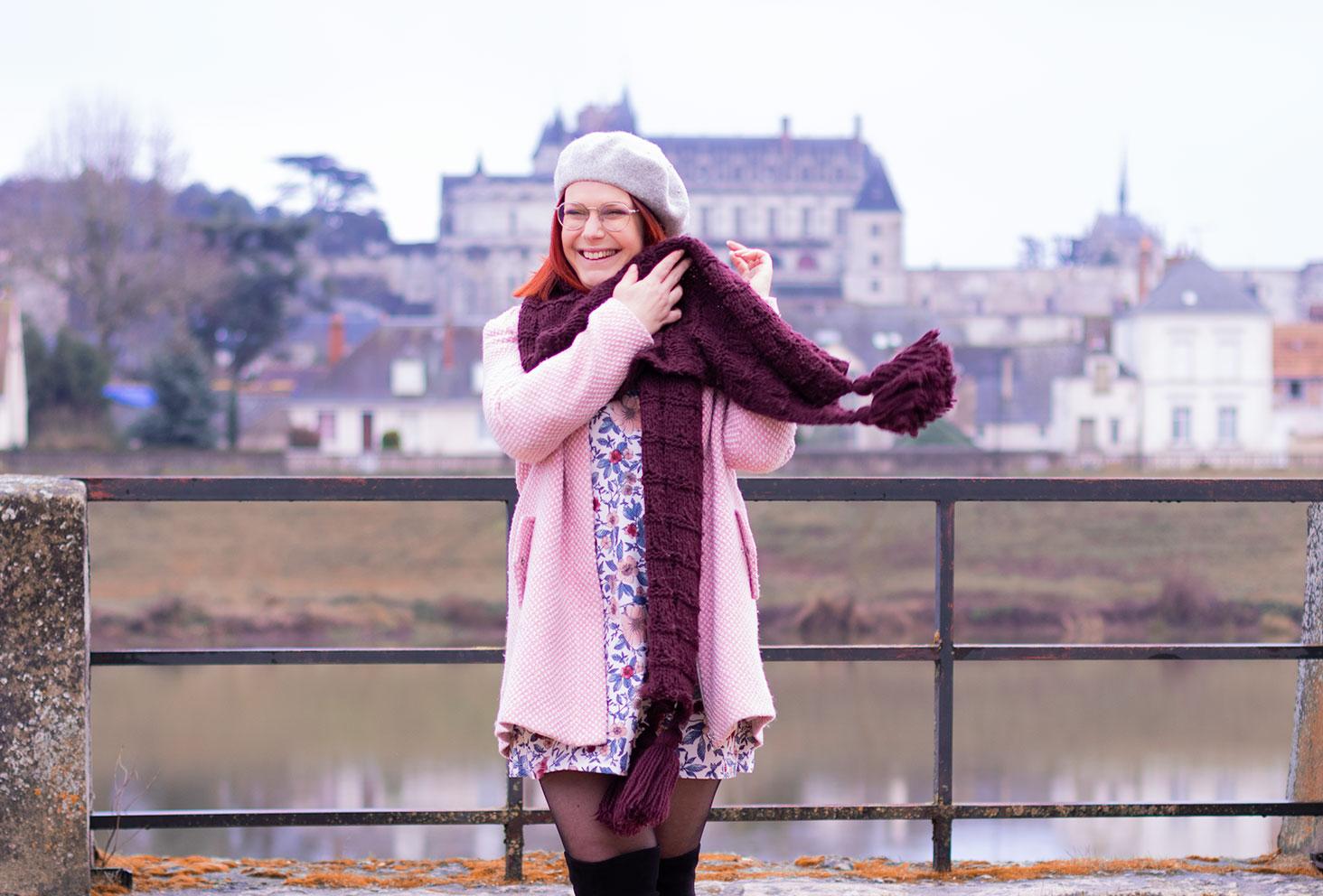 Devant le château d'Amboise, en train de remettre l'écharpe en laine bordeaux sur le manteau rose