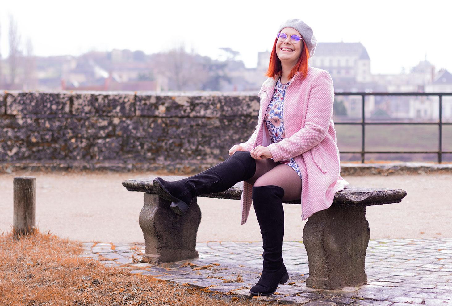 En train de remettre les cuissardes en place, assise sur un banc en manteau rose, devant le château d'Amboise