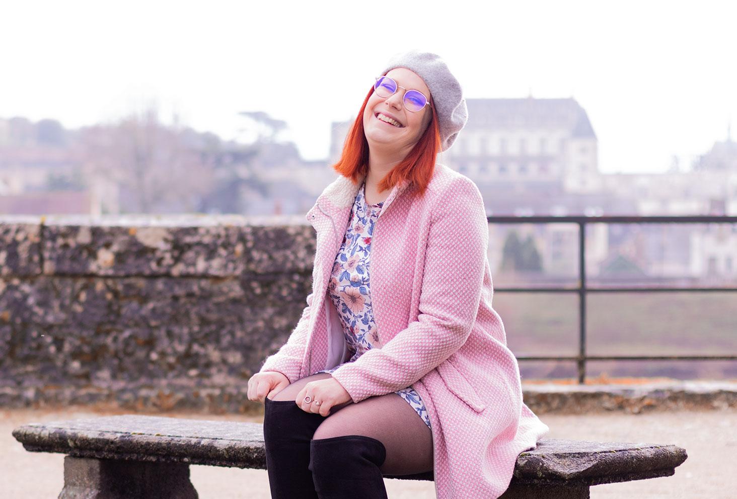 Assise sur un banc avec le château d'Amboise dans la brume en arrière plan, en manteau rose et robe à fleurs