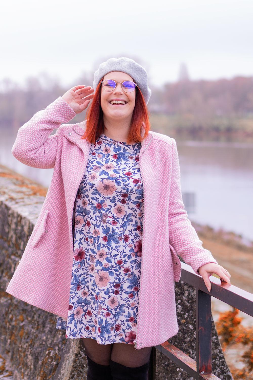 Appuyé le long d'une rambarde sur les bords de Loire, en manteau rose et robe à fleurs, un béret sur la tête et le sourire aux lèvres