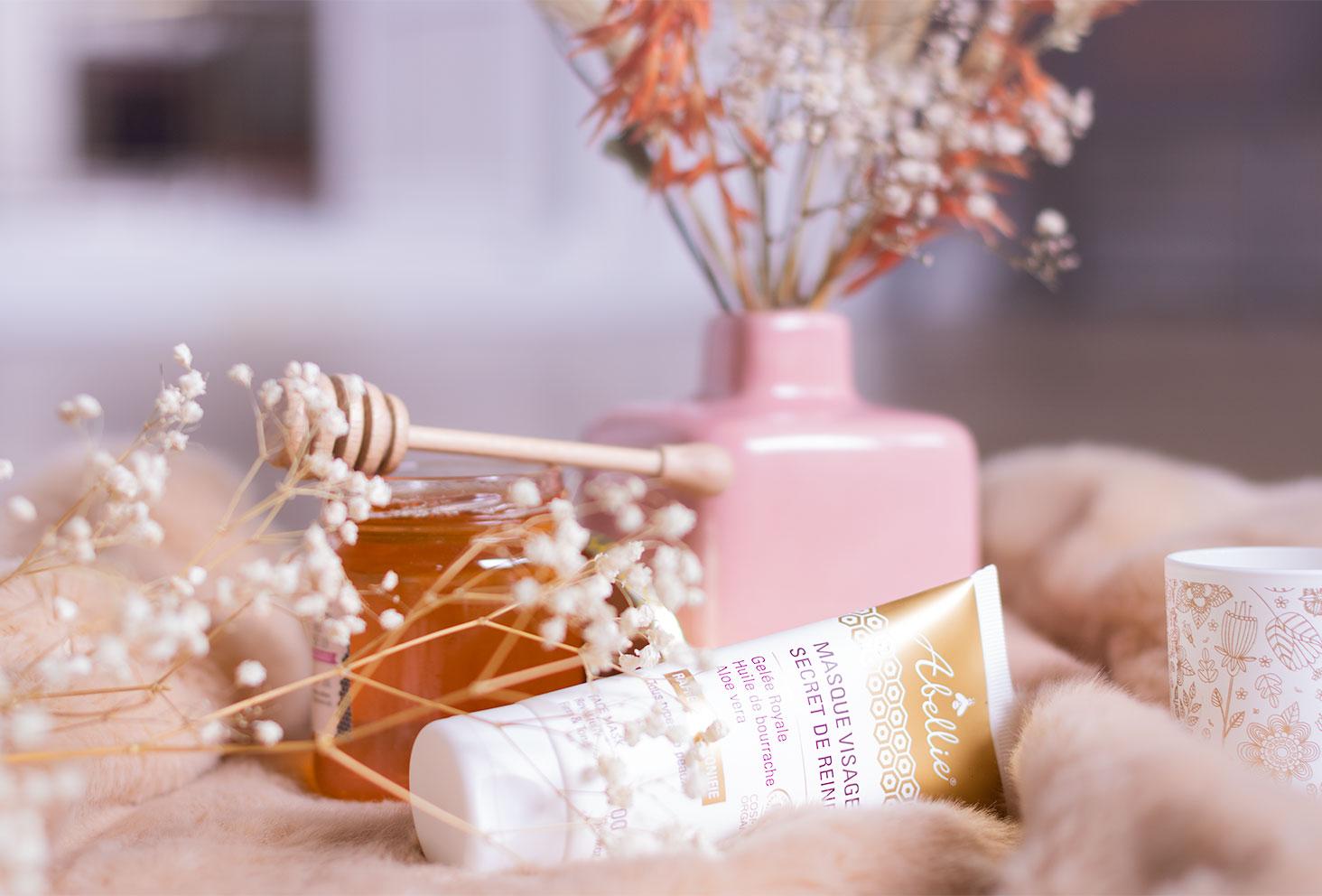 Le masque visage Abellie couché sur un plaid rose au milieu de miel et de fleurs sèches