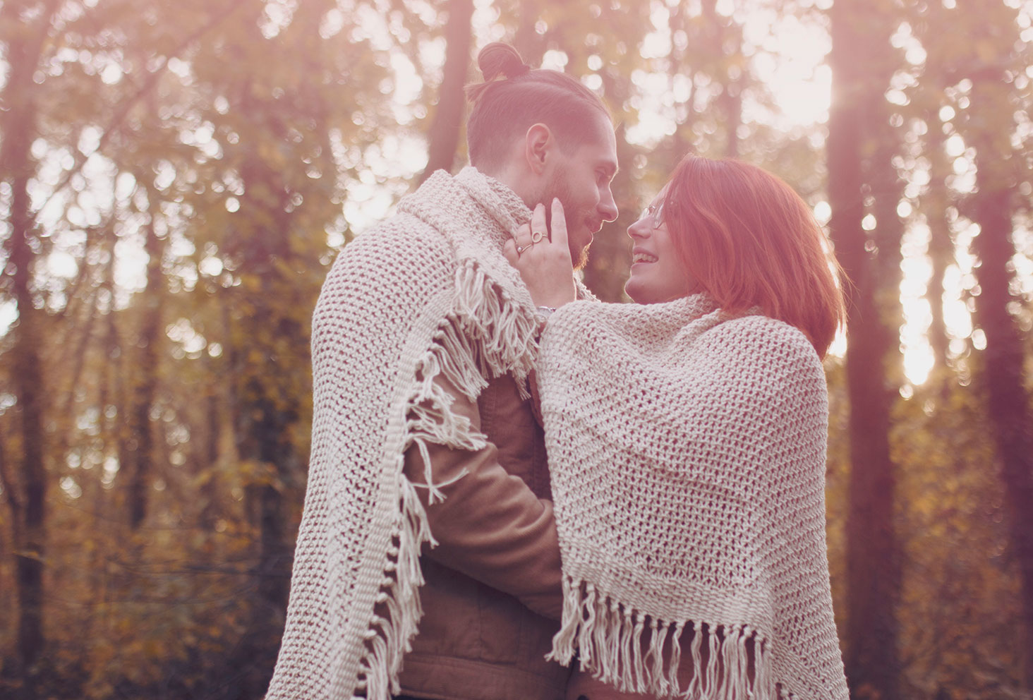 Photo de couple en forêt, emmitouflés dans un plaid en mailles beiges, sous le soleil d'automne
