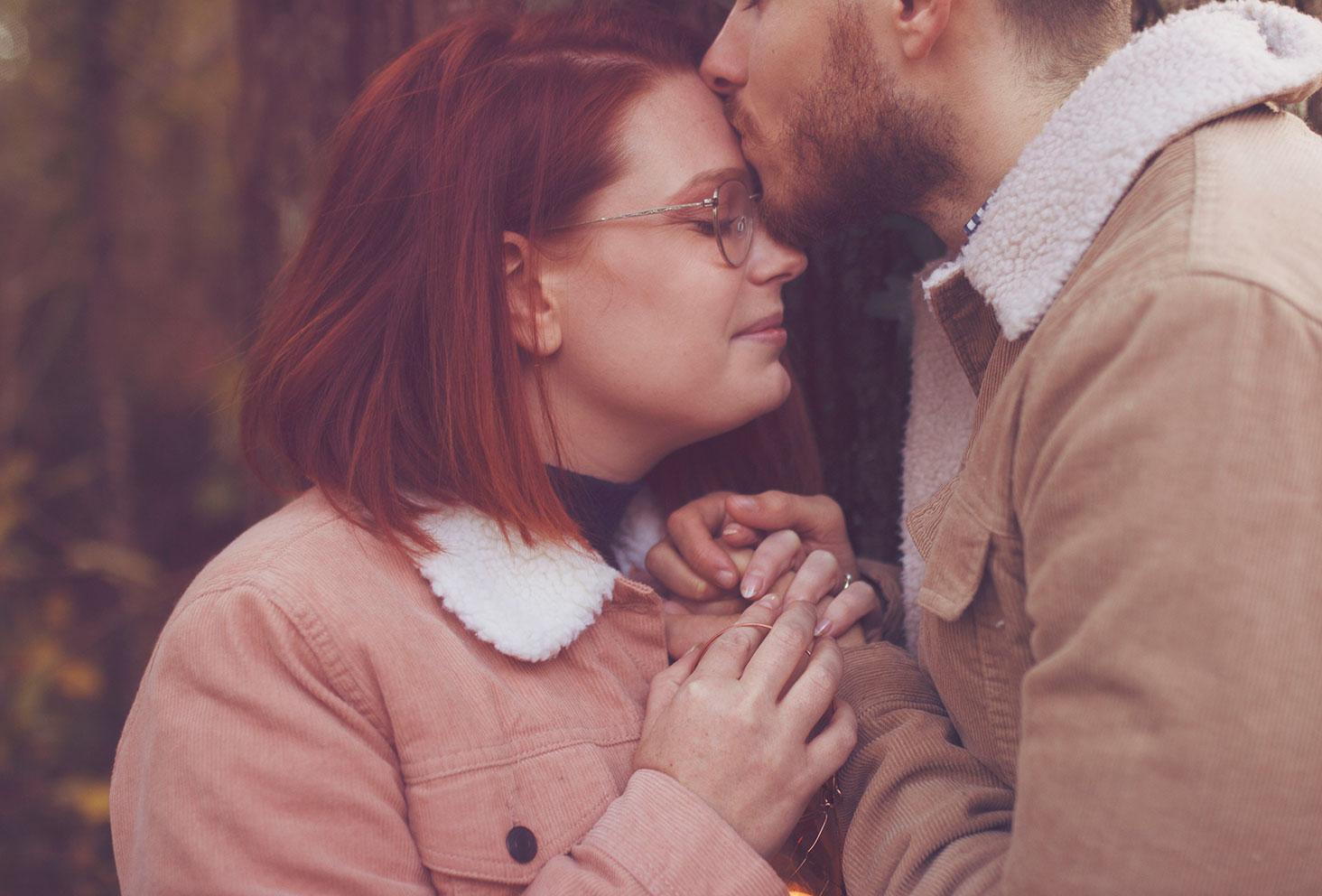Bisou d'amoureux sur le front pendant des photos de couple au milieu de la forêt en automne