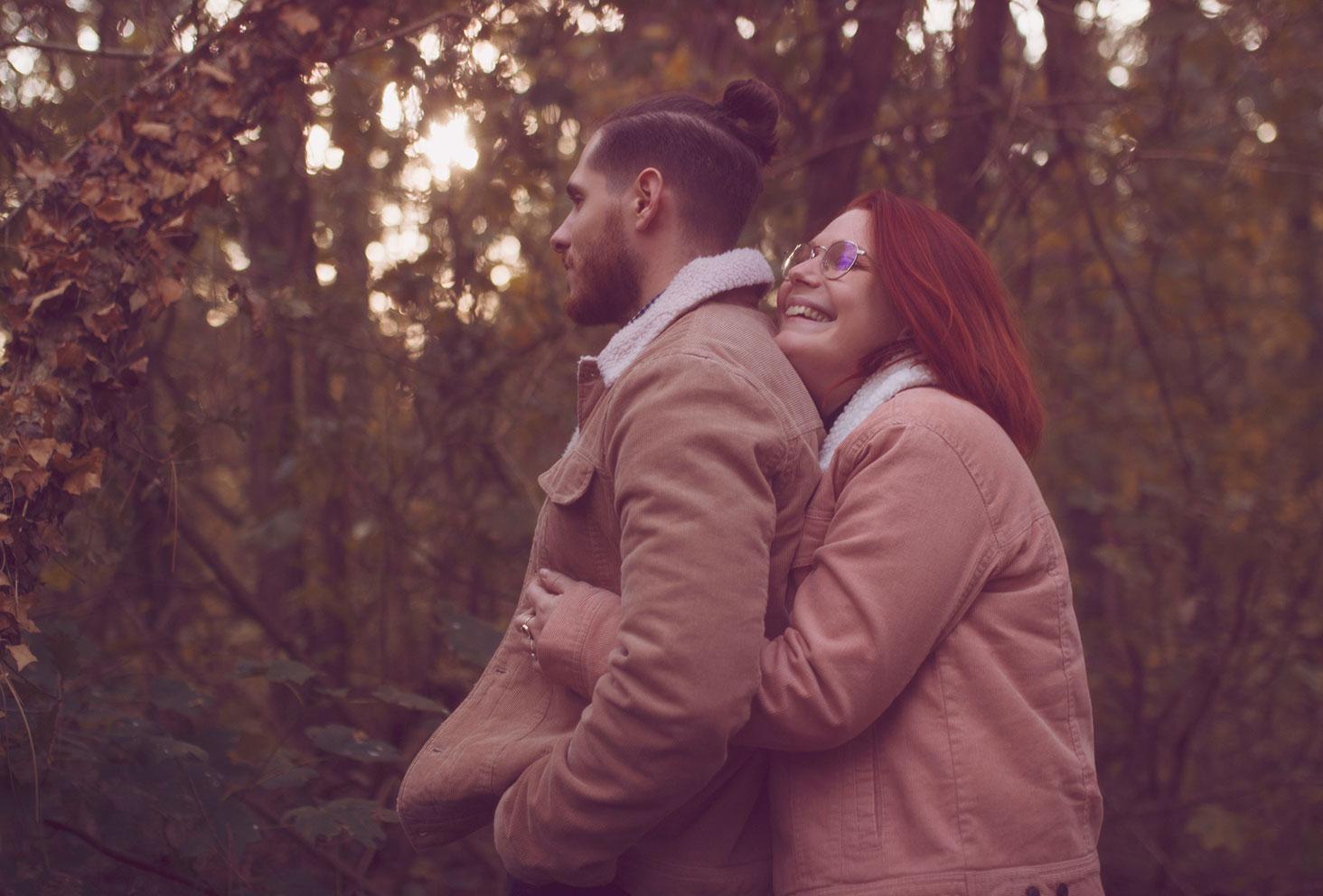 Câlin de couple au milieu de la forêt aux couleurs de l'automne, durant une séance photo amoureux