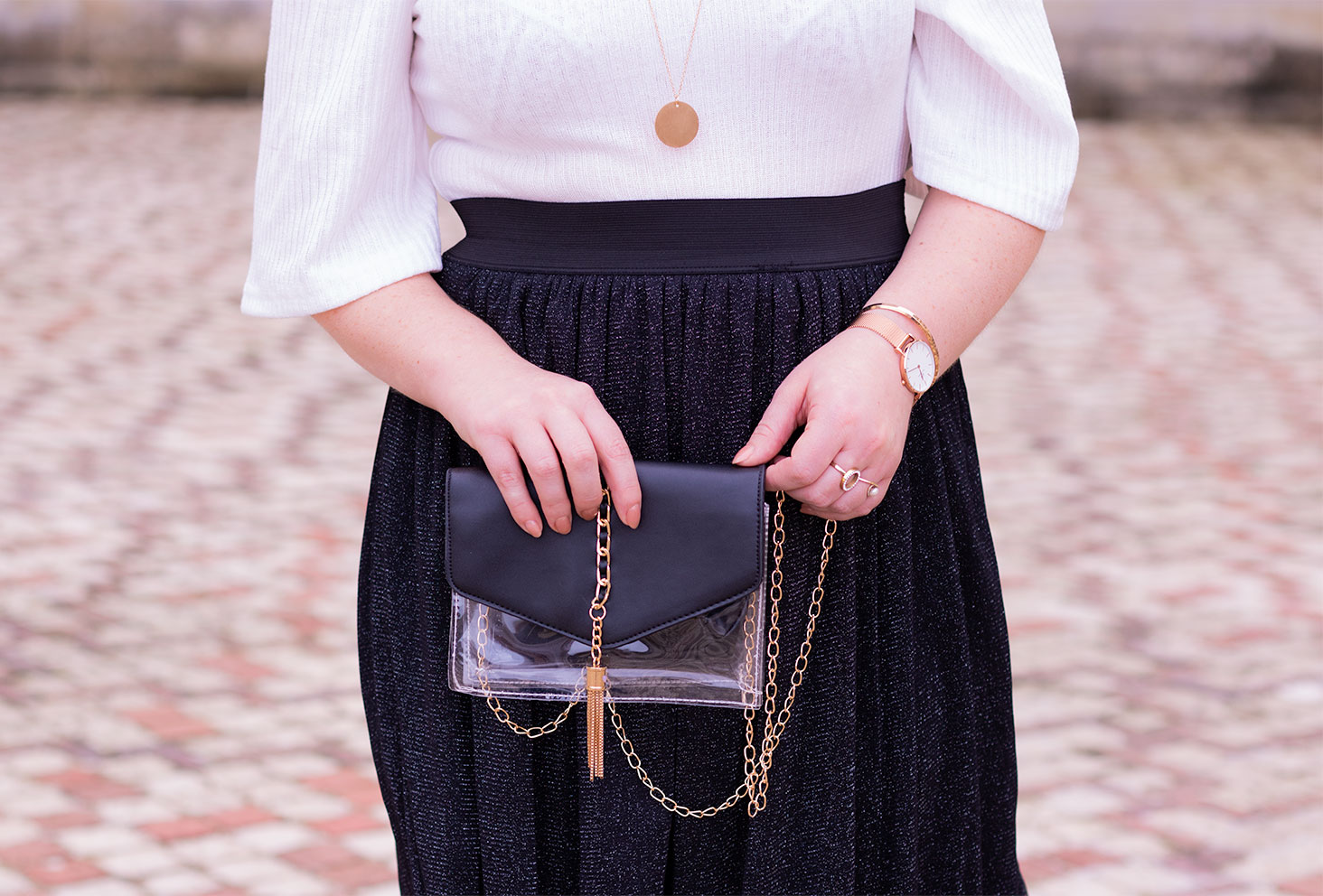 La pochette transparente noire et dorée SheIn entre les mains, devant une jupe en tulle noir pailletée