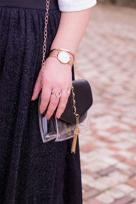 La pochette transparente portée au bras, une main posé dessus, la Melrose dorée de Daniel Wellington au poignet