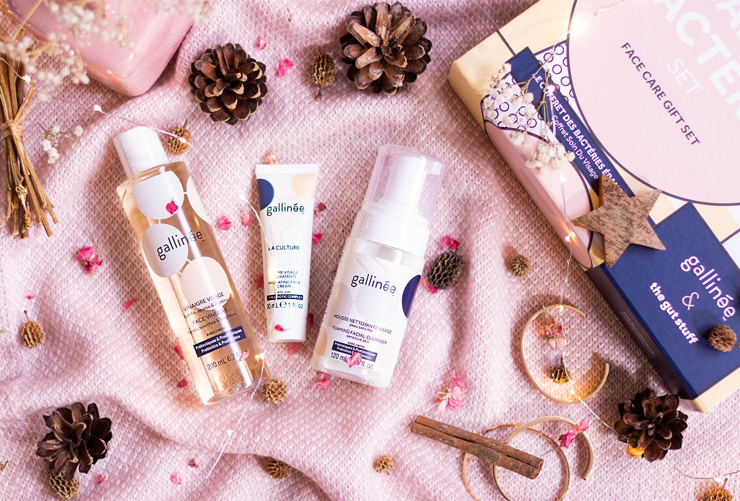 Trois produits d'un joli coffret de la marque Gallinée sur un plaid rose au milieu des guirlandes et des décorations de Noël