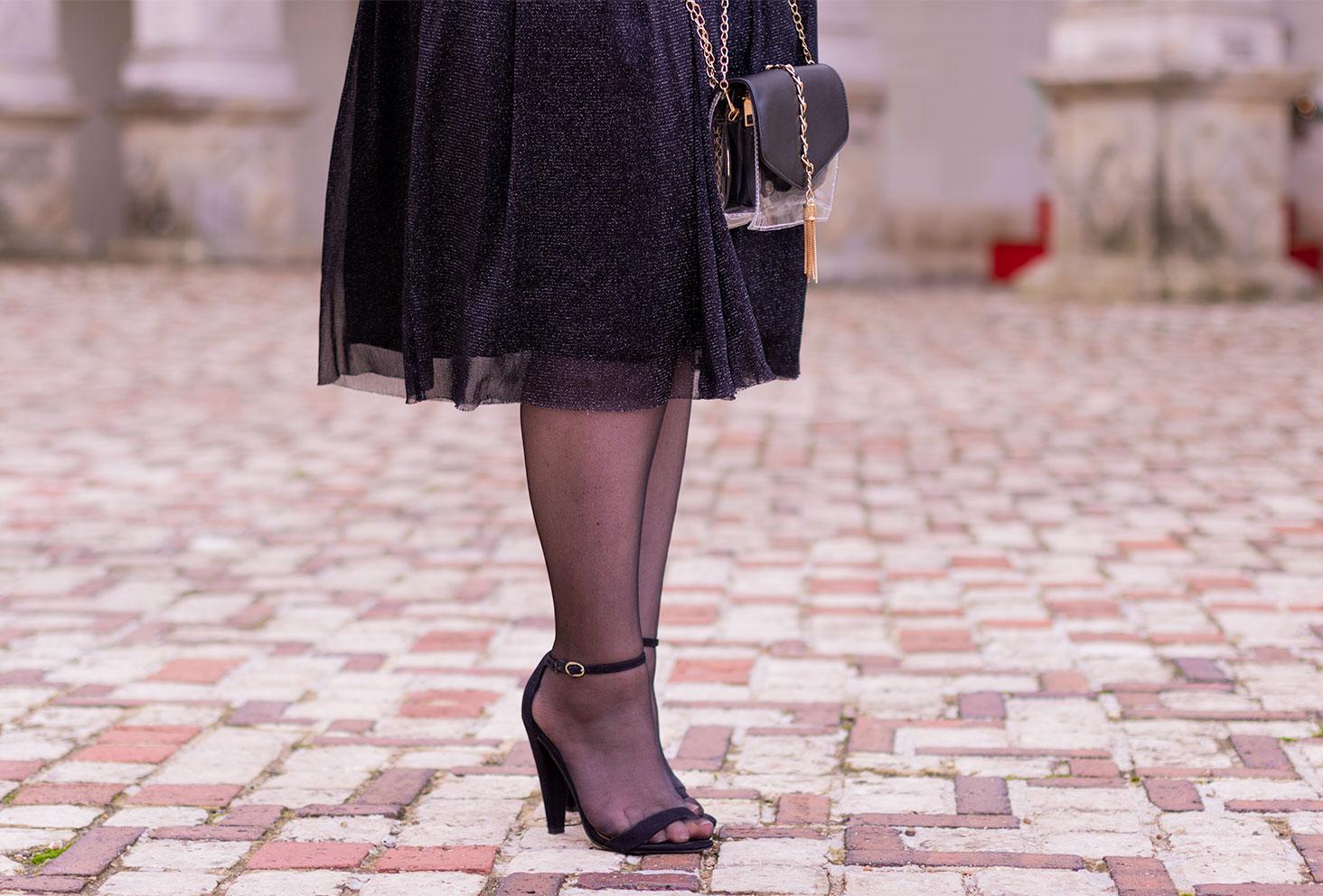 Sandales à talons hauts noirs portés avec une jupe tutu à paillettes, sur les pavés du château de Villandry