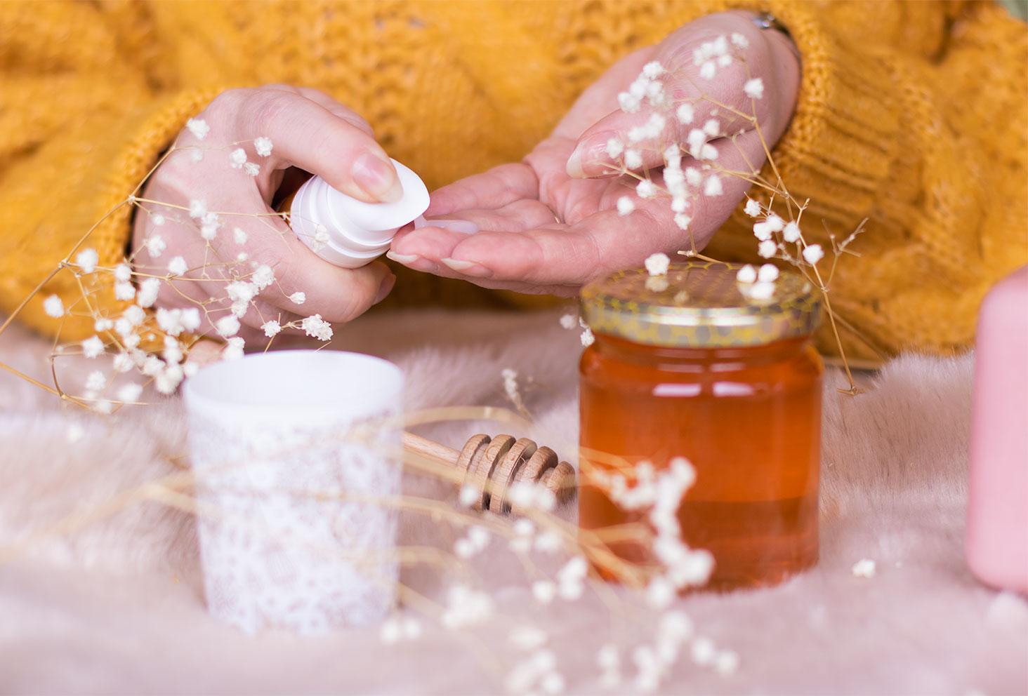 La texture du sérum pour le visage Abellie dans la main tout juste sorti de la pompe, au milieu de fleurs sèches et de miel