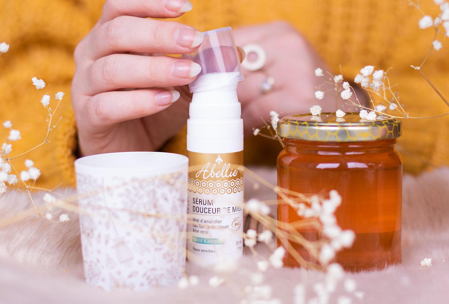 Zoom sur le sérum pour le visage Abellie, au milieu de fleurs sèches et de miel