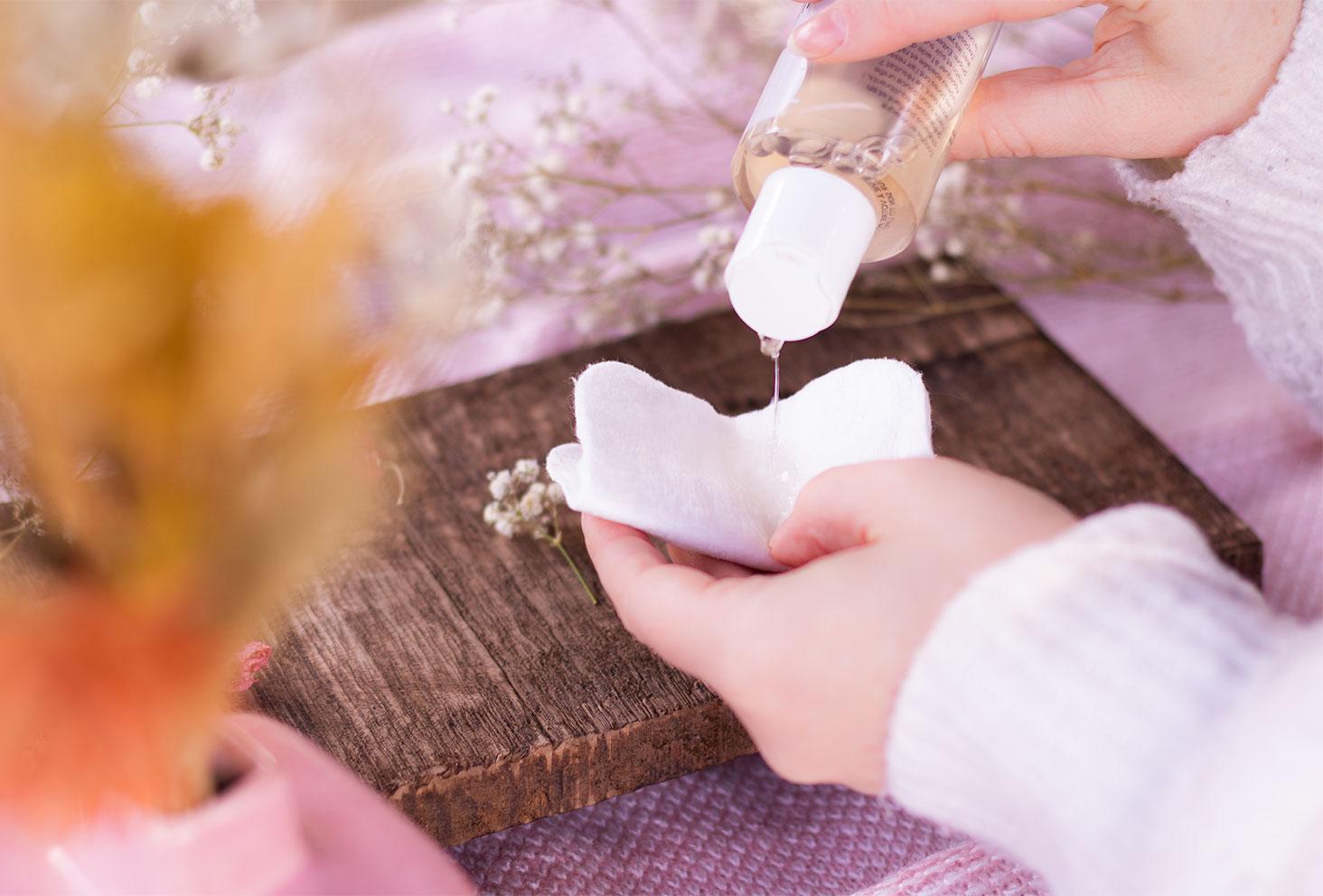 Zoom sur la texture liquide du vinaigre visage de Gallinée, en pleine utilisation sur un coton, au dessus d'une planche en bois et des fleurs sèches