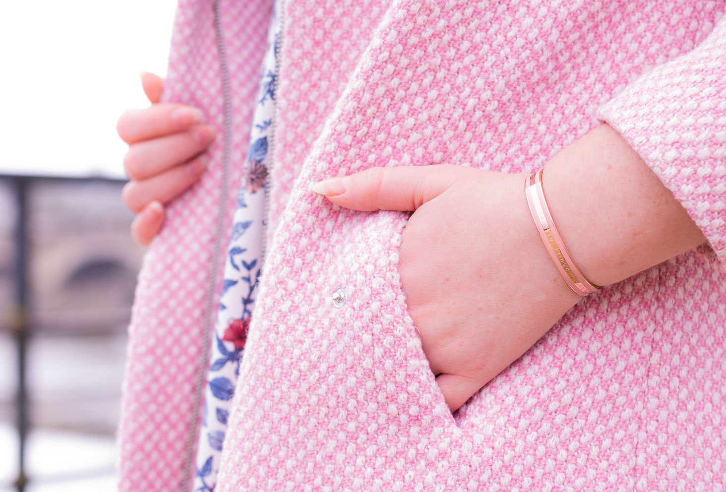 Zoom sur le bracelet Classic rose de Daniel Wellington, la main dans la poche d'un manteau rose bonbon