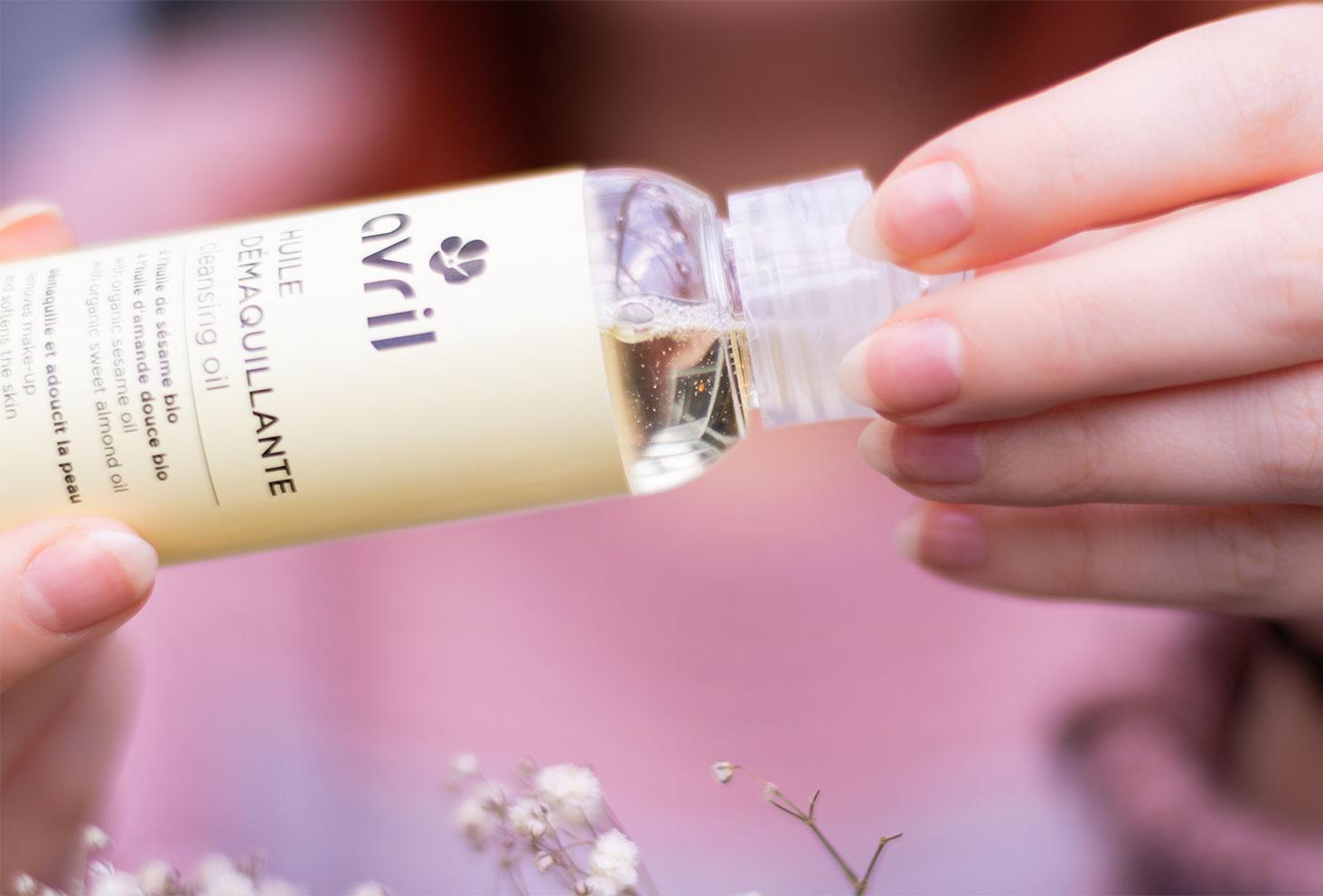 Zoom sur la texture de l'huile démaquillante Avril tenue dans les mains au-dessus de fleurs séchées