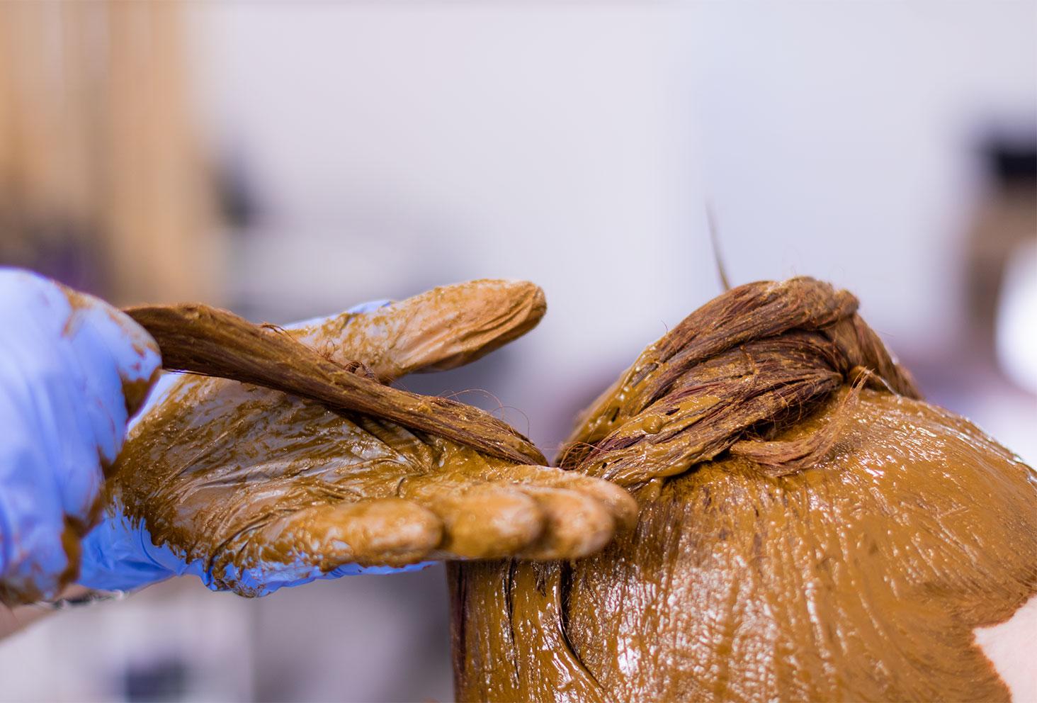Application de la coloration végétale au henné naturel avec les mains sur l'ensemble des cheveux au salon de coiffure Artiste en Herbes à Tours