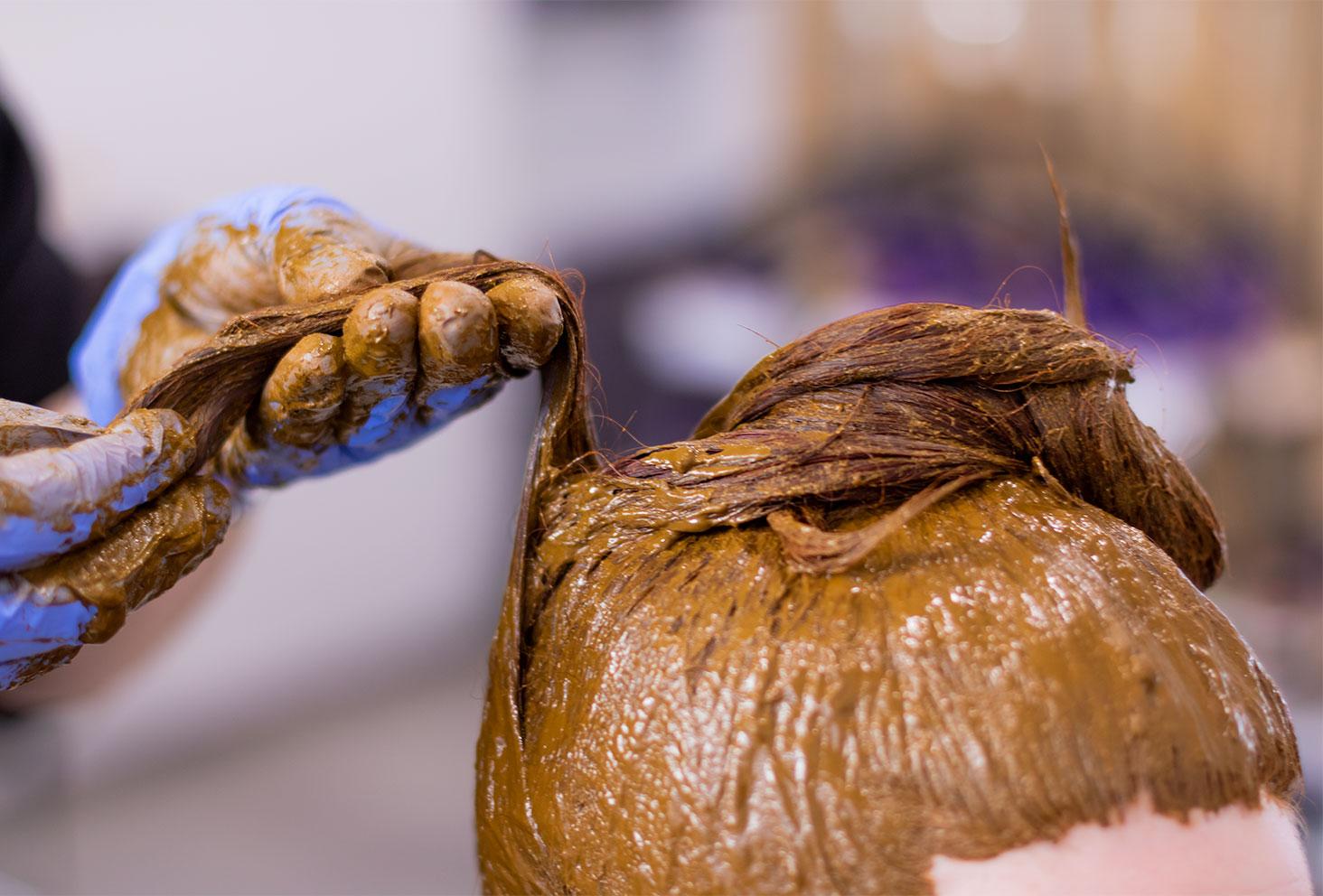 Application de la coloration végétale au henné naturel avec les mains sur l'ensemble des cheveux