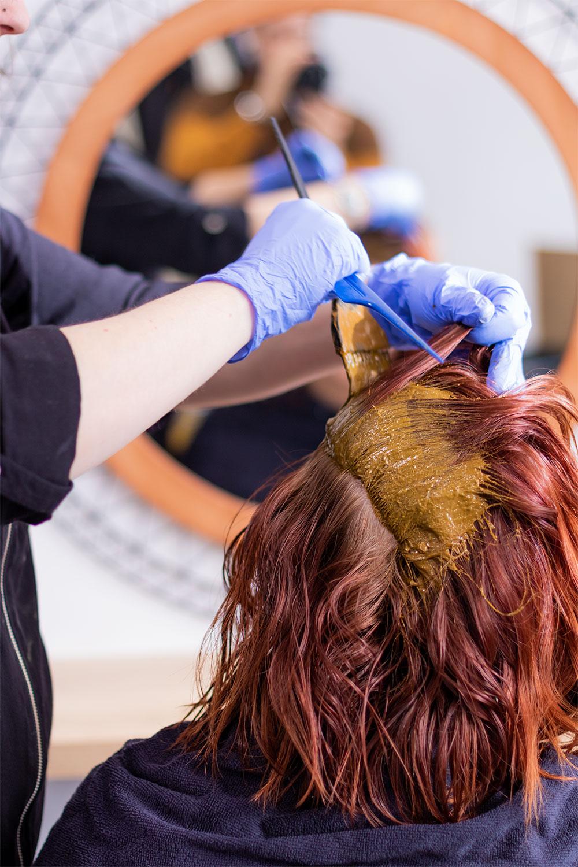 Application de la coloration végétale sur cheveux roux au pinceau au niveau des racines