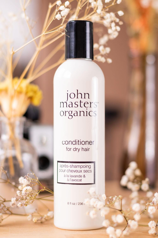 La bouteille blanche de l'après-shampooing pour cheveux secs de la marque John Masters Organics posé sur un bureau au milieu de fleurs séchées et devant des objets vintages