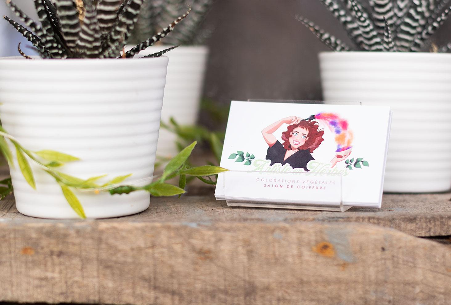 Les cartes de visite du salon de coiffure Artiste en Herbes à Tours posé sur une caisse en bois au milieu de plantes grasses