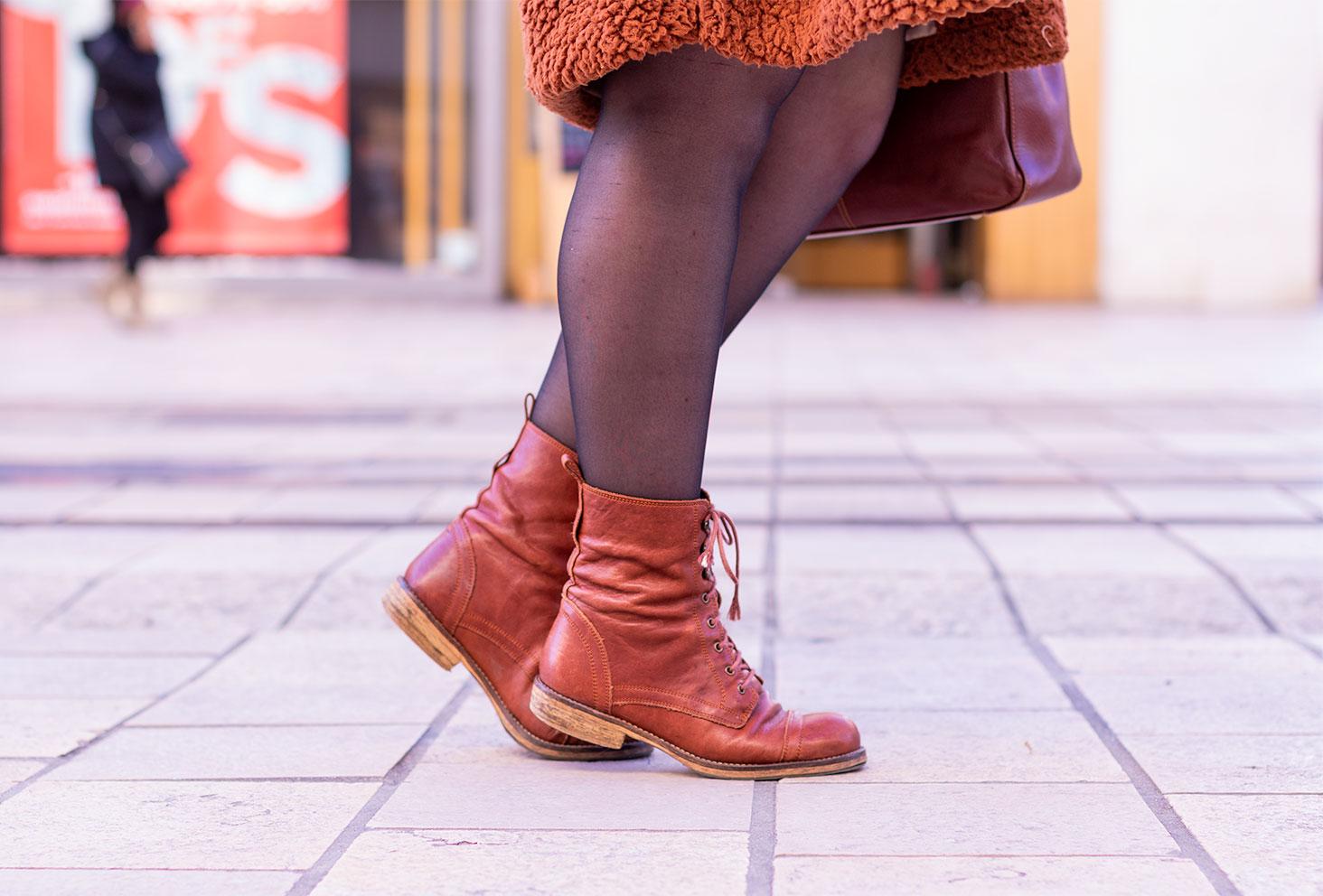 Zoom sur les boots à lacets camel de la marque Jonak portées en pleine rue en train de marcher