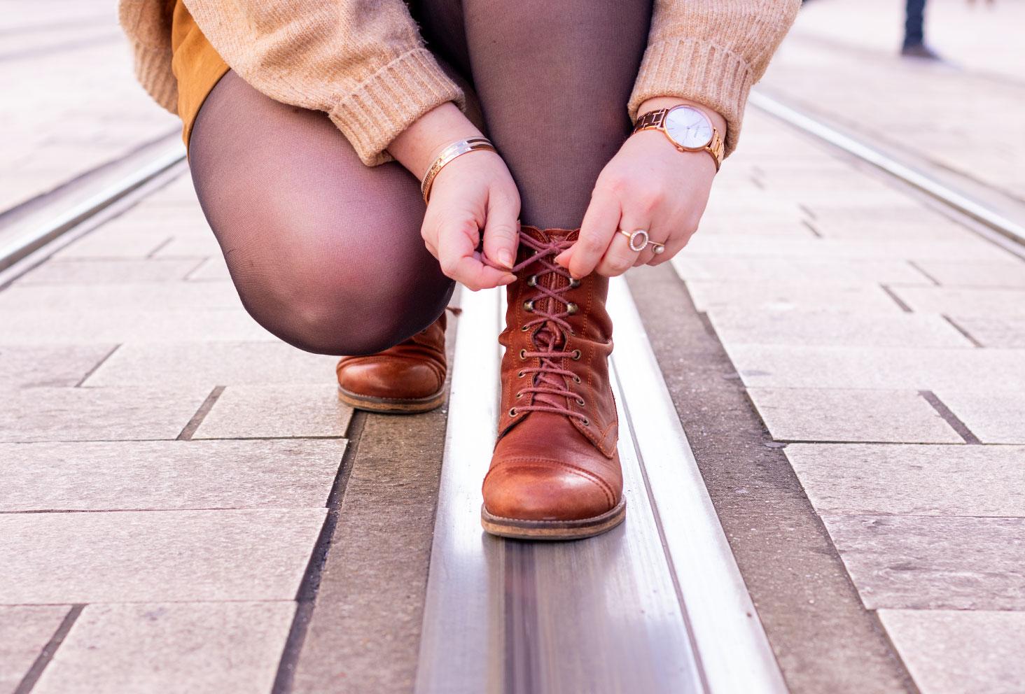 Les bottines à lacets en cuir marron de la marque Jonak, portées de face les lacets entre les mains