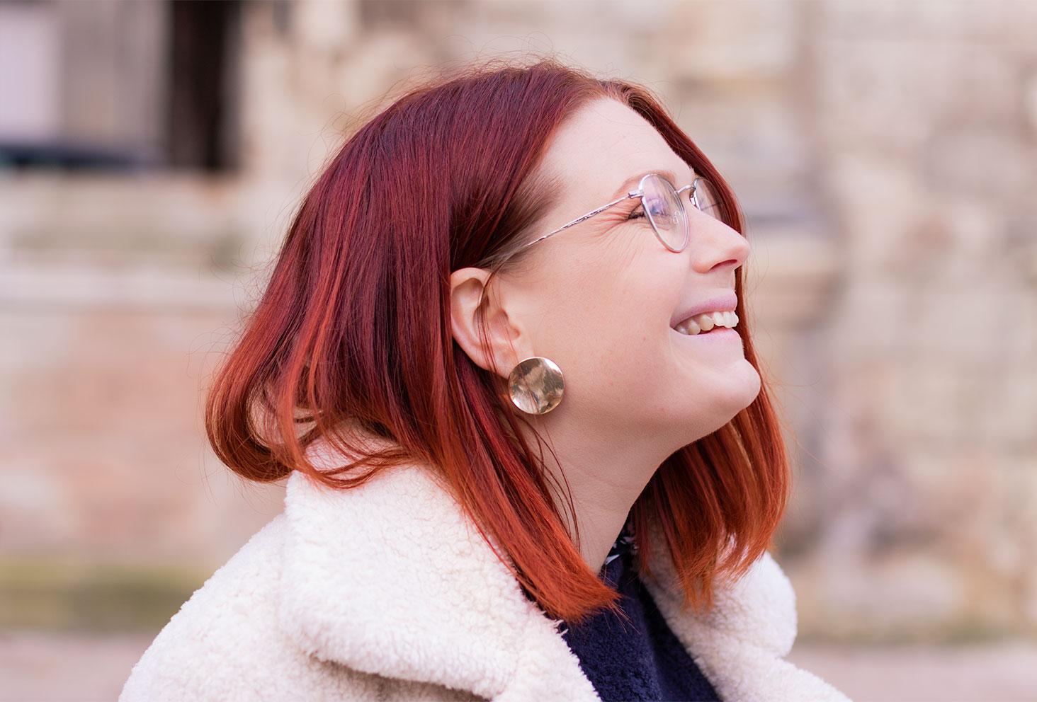 De profil en manteau moumoute blanc, des boucles d'oreilles médaillons dorées aux oreilles