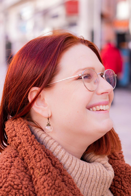 De profil avec le sourire, dans un manteau marron en moumoute, des boucles d'oreilles en verre a pissenlit aux oreilles