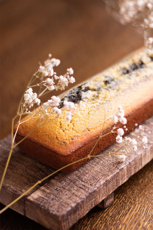 Zoom sur la croûte du cake marbré au sésame noir sur une planche en bois derrière des fleurs sèches blanches