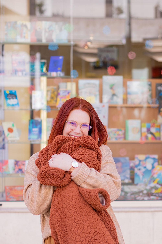 Devant une vitrine de livres, avec le sourire, serrant bien fort un manteau en fausse fourrure marron Shein entre les bras