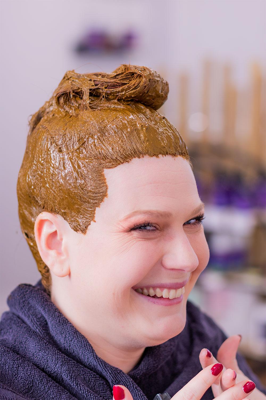 La tête recouverte de coloration végétale au henné naturel dans le salon de coiffure Artiste en Herbes à Tours, de profil avec le sourire