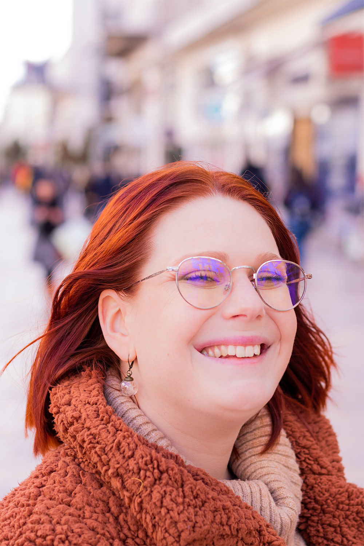 Au milieu de la rue avec le sourire, zoom sur le col du manteau moumoute marron de la marque Shein