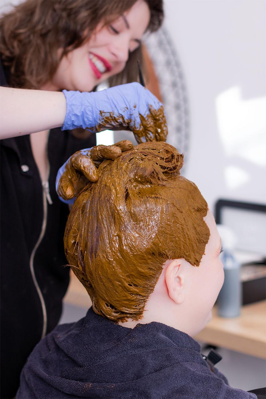 Application au pinceau de la coloration végétale au henné naturel sur l'ensemble des cheveux.