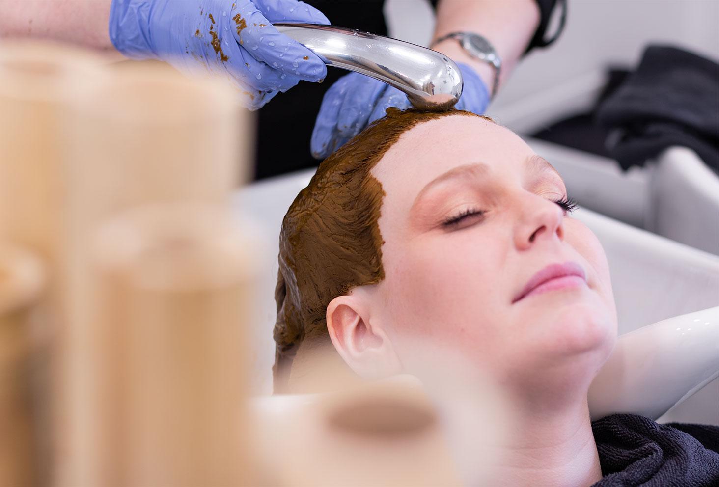 Rinçage de la coloration végétale au henné naturel sur les cheveux, au bac dans le salon de coiffure