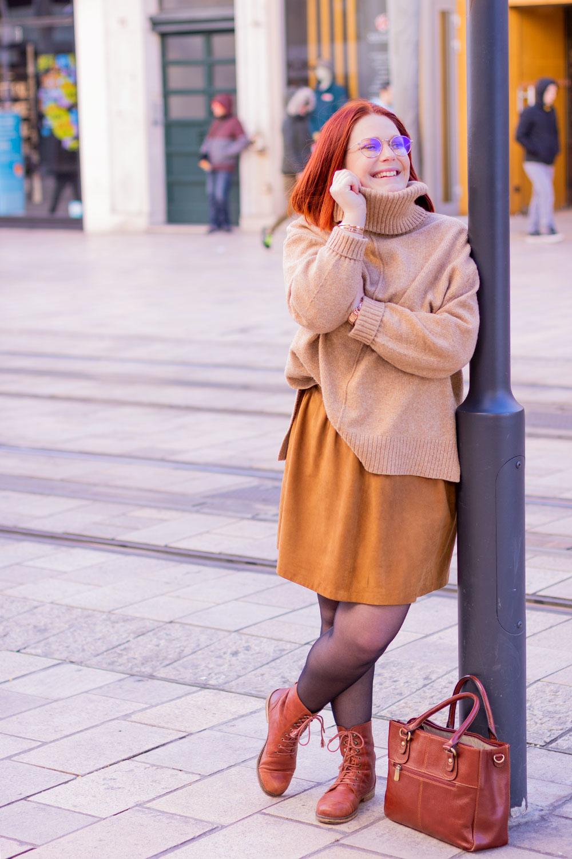 Appuyée à un poteau au milieu de la rue, en pull à col roulé beige et jupe Caramel, un sac en cuir marron posé aux pieds
