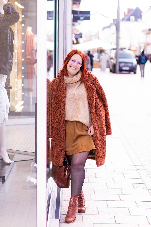 De profil contre la vitrine d'un magasin, au milieu d'une grande rue, avec un manteau sur les épaules