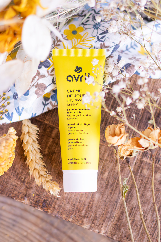 La crème de jour Avril de haut posée sur une planche en bois au milieu de fleurs séchées jaunes