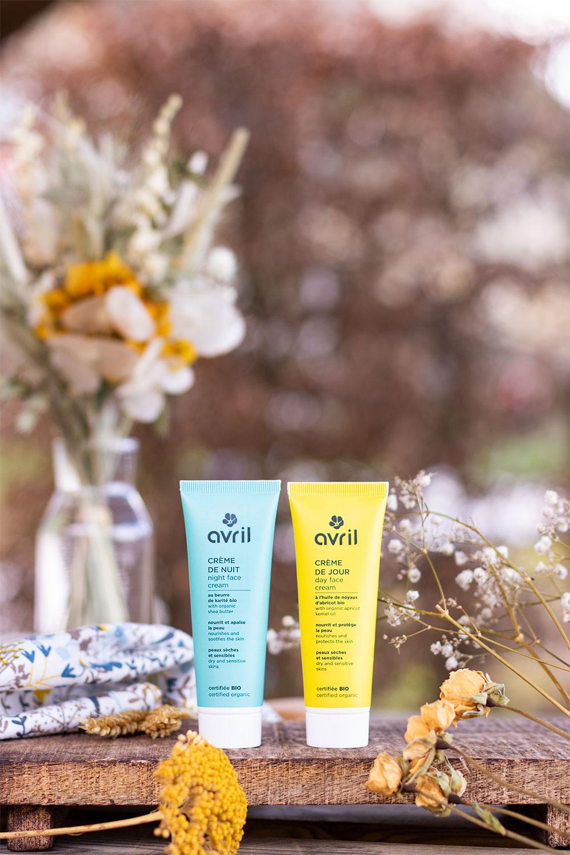 La crème de nuit bleue et la crème de jour jaune, debout sur une planche en bois, entourées de fleurs séchées jaunes et blanches