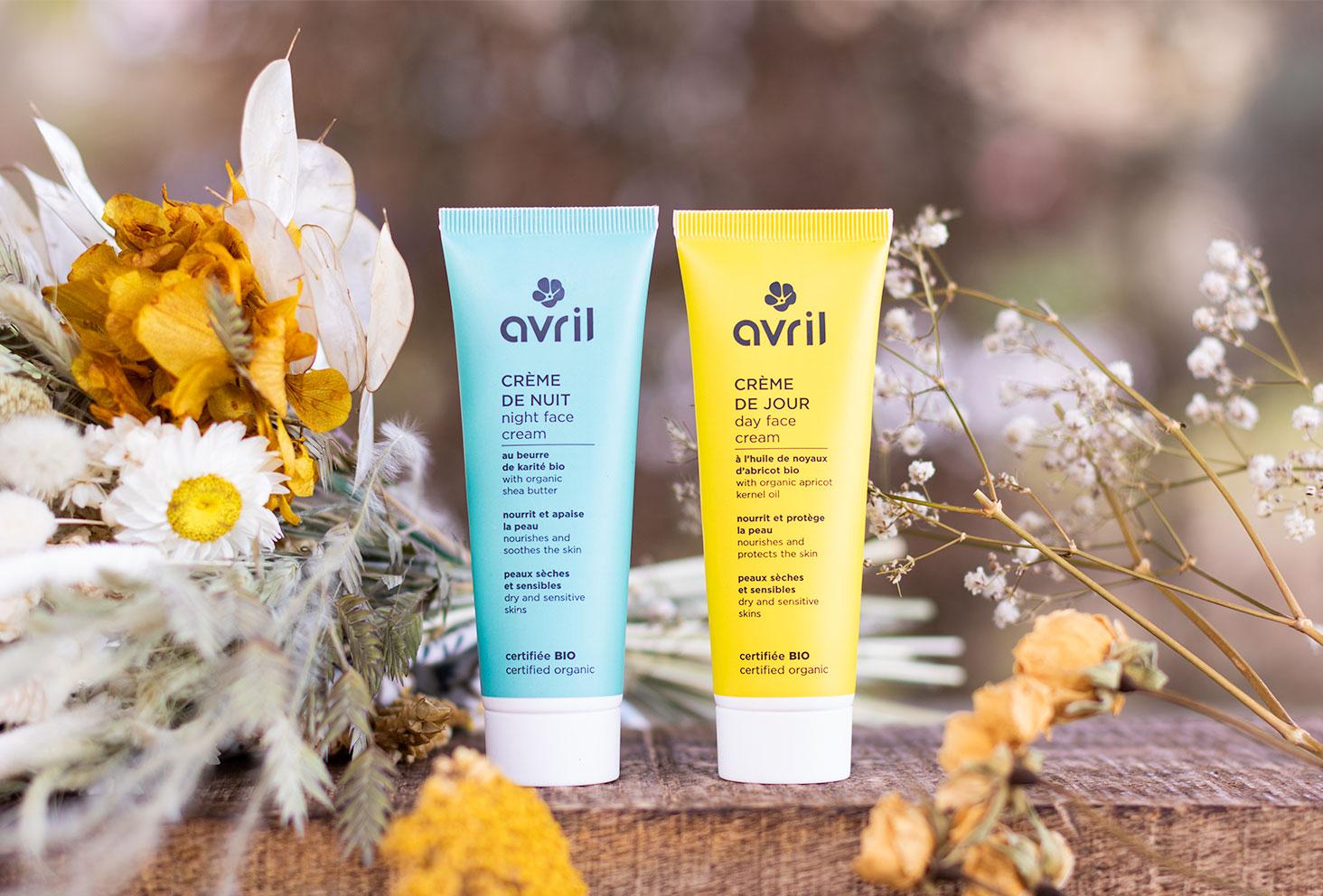 La crème de jour jaune et la crème de nuit bleue, posées sur une planche en bois au milieu d'un bouquet de fleurs séchées jaune et blanc