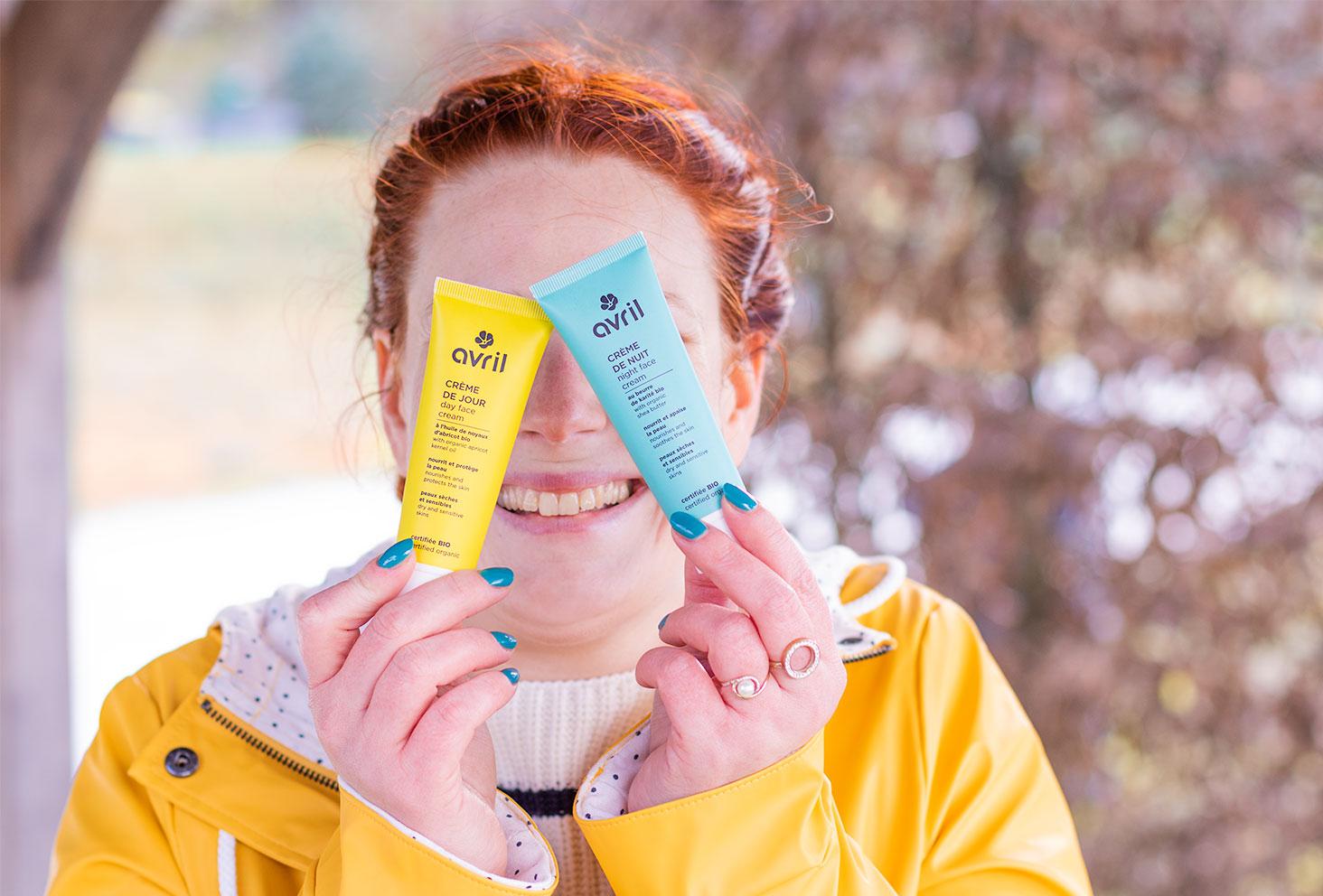 La crème de jour et la crème de nuit de la marque Avril, tenues dans les mains devant les yeux avec le sourire, en ciré jaune et vernis turquoise sur les ongles