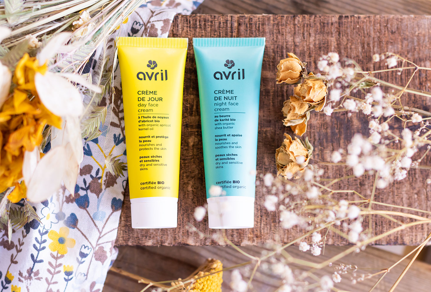 La crème de jour et la crème de nuit Avril posées sur une planche en bois de haut au milieu de fleurs sèches jaunes et blanches