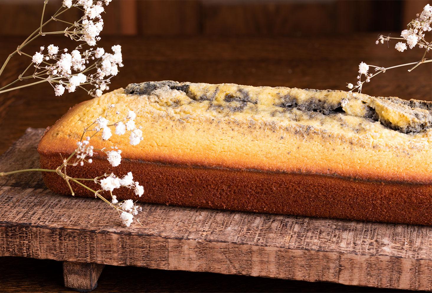 Recette d'un cake marbré à l'orange et à la crème de sésame noir, posé sur une planche en bois brut