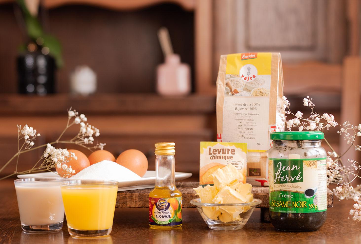 Les ingrédients nécessaires à la réalisation d'un cake marbré à l'orange et à la crème de sésame noir, posé sur une table en bois au milieu de fleurs sèches blanches
