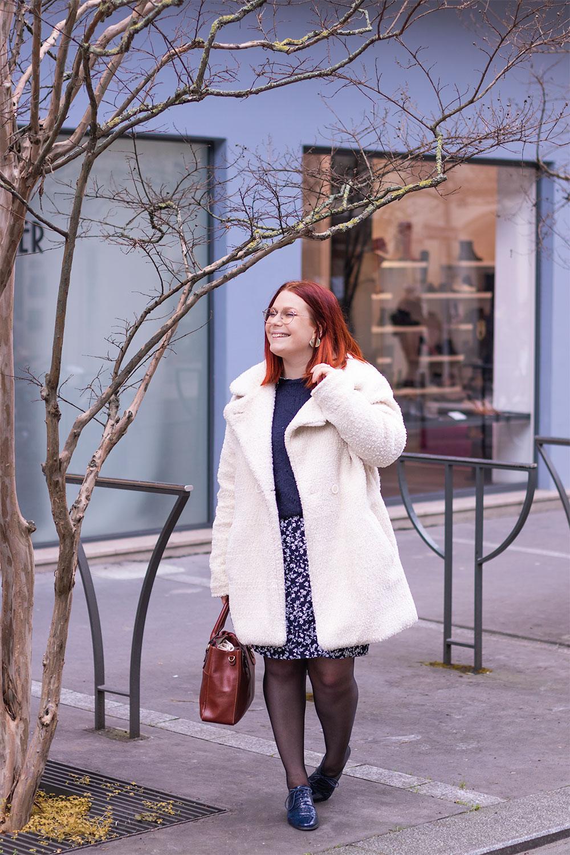 Manteau blanc, robe chemise à fleurs, pull à grosses maille, derbies bleues et sac à main marron pour un look de bonnes résolutions 2019
