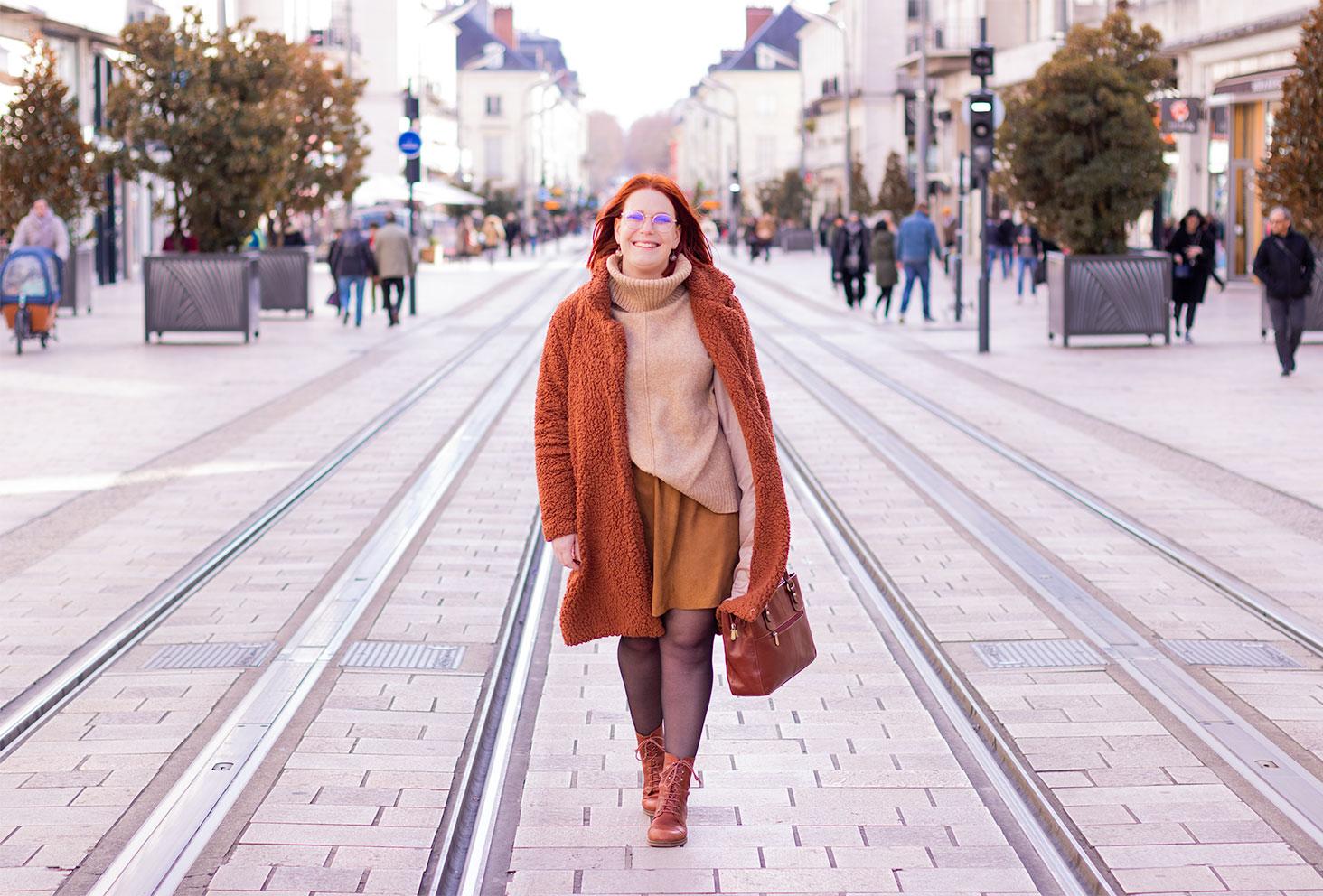 En train de marcher au milieu de la grande rue Nationale de Tours, en manteau marron Shein, le sac à main au bras et le sourire au lèvres