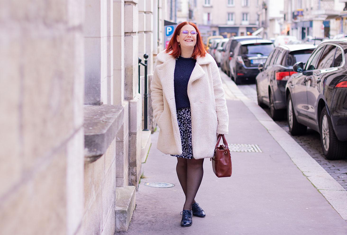 Look en manteau blanc sur le trottoir dans la rue près des voitures