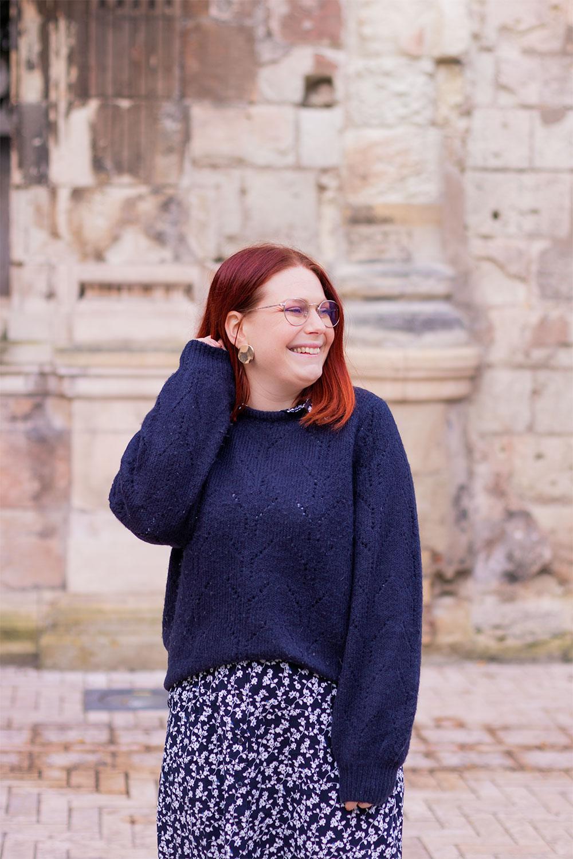 En pull bleu par dessus une robe chemise bleue à fleurs, la main dans les cheveux, devant un mur en ruines