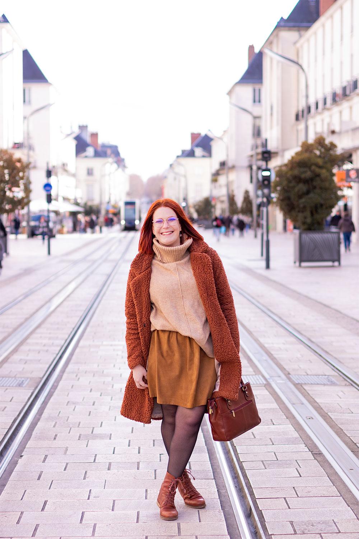 Au milieu de la rue Nationale à Tours, en jupe en cuir et boots à lacets, les jambes croisée un sac marron à la main