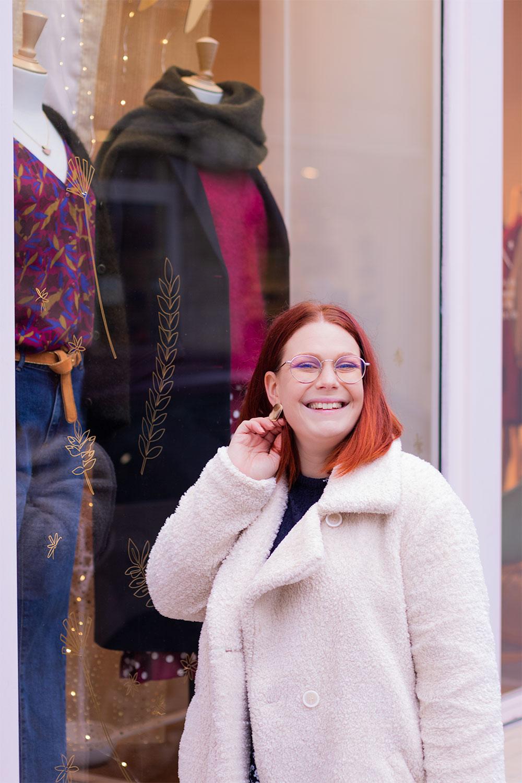 Devant la vitrine d'un magasin, la main dans les cheveux, en manteau moumoute beige