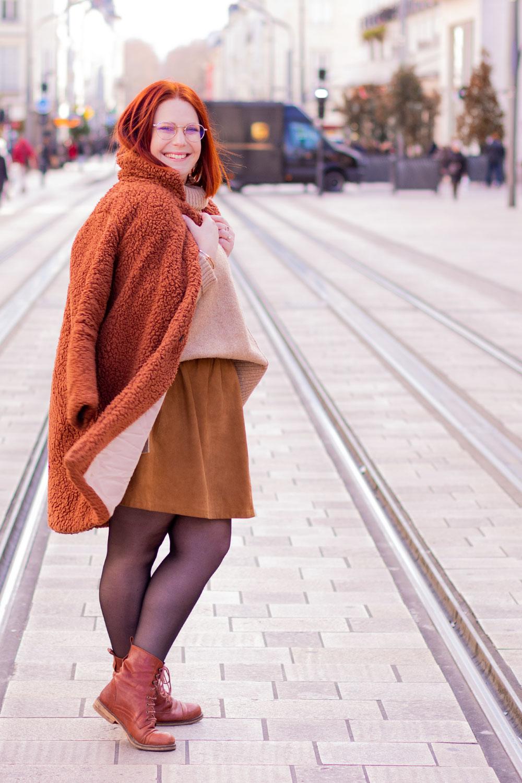 De profil au milieu d'une grande rue, avec un manteau en fausse fourrure marron de la marque Shein posé en cape sur les épaules