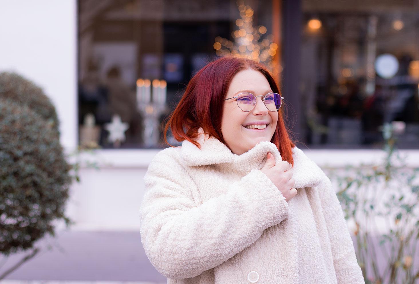 En manteau moumoute beige fermé, devant une vitrine illuminée pour Noël