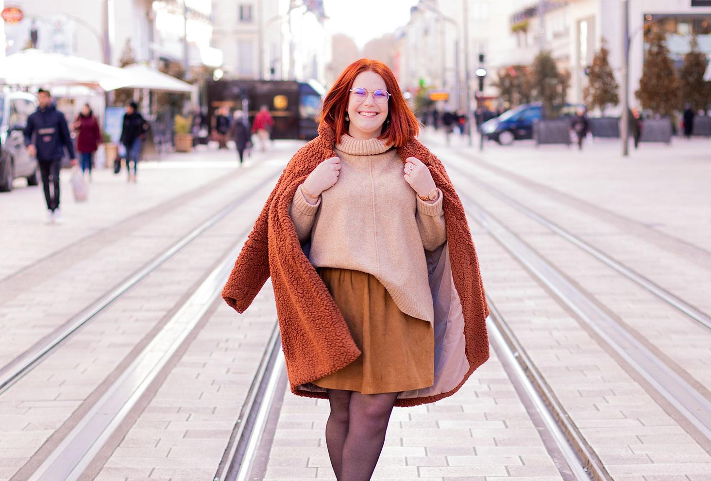 Au milieu d'une grande rue avec un manteau marron sur les épaules, en pull à col roulé et jupe qui tourne